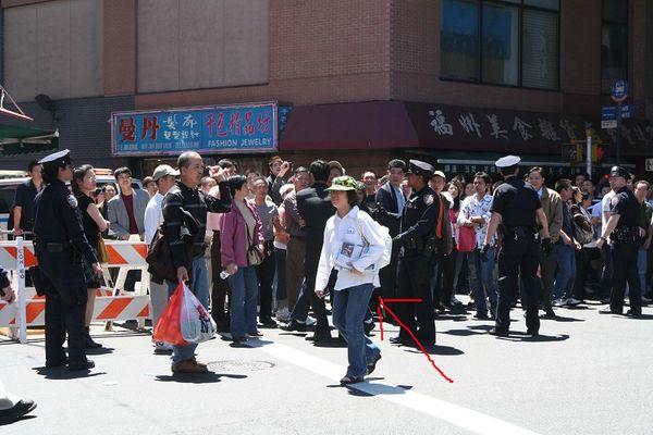 Последовательница Фалуньгун, распространяющая газеты и листовки, на которую потом напал хулиган. Фото: The Epoch Times