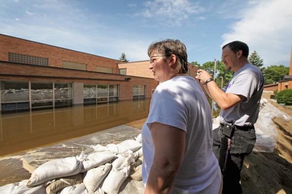 Учительница школы Св. Терезы и падре Фред Харвер обозревают повреждения здания школы от наводнения. г. Майнот, Северная Дакота, США. Фото: Scott Olson/Getty Images