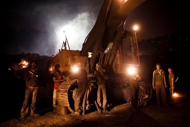 Рабочие чинят сломавшийся экскаватор. Фото: Daniel Berehulak/Getty Images