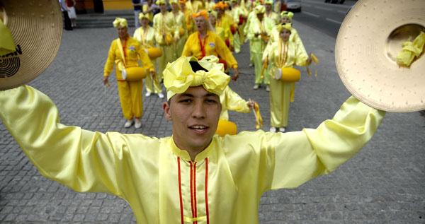 Хлопець із тарілками задає ритм групі барабанщиків у параді послідовників Фалуньгун. Фото: The Epoch Times