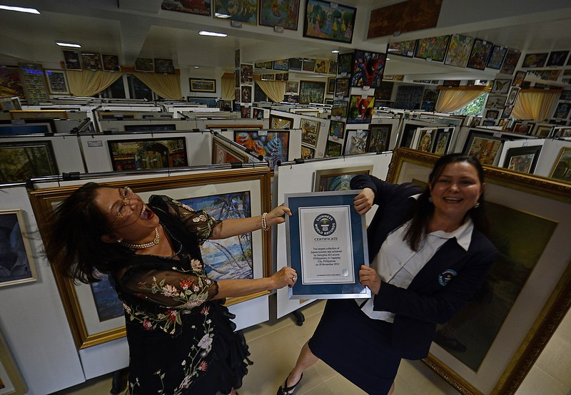 Тагайтай, Филиппины, 29 ноября. Коллекция картин-паззлов Джорджины Джилл-Лакуны (слева), насчитывающая свыше тысячи «шедевров», признана крупнейшей в мире и занесена в Книгу рекордов Гиннесса. Фото: TED ALJIBE/AFP/Getty Images