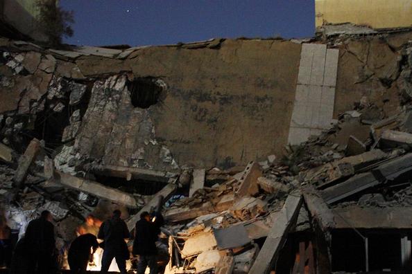 Уничтожено здание, а в городе разрушены квартиры мирных жителей. Люди стоят возле обломков ракеты на груде мусора после ракетного удара, полностью разрушившего административное здание резиденции Муамара Каддафи в Триполи 20 марта 2011 года. Здание, нахо