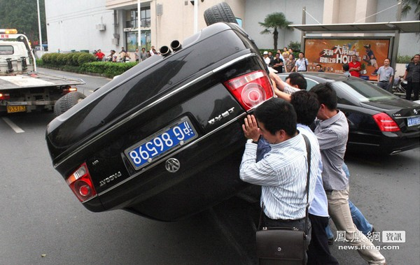 Водій, маневруючи, не впорався з керуванням і його автомобіль, наїхав на бордюр і перекинувся. Перехожі допомагають повернути автомобіль у експлуатаційне положення. Місто Нанкін. Вересень 2011. Фото: news.ifeng.com