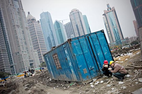 Китайские рабочие обедают на строительной площадке в Шанхае 5 февраля 2010. Фото: PHILIPPE LOPEZ/AFP/Getty Images