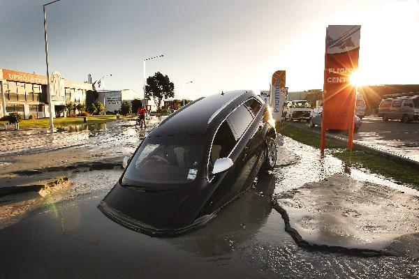 Нова Зеландія, м. Крайстчерч, 13 червня 2011 г.: машина впала у воду на ул.Феррі після другого поштовху магнітудою 6,0 балів. Фото: Martin Hunter/Getty Images