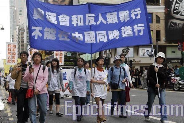 Гонконг. Шествие в поддержку Всемирной эстафеты факела в защиту прав человека. Надпись на плакате: «Олимпиада не может проводиться в Китае вместе с преступлениями против человечности». Фото: Ли Чжунюань/ The Epoch Times