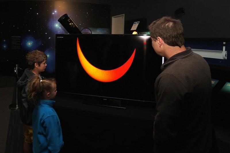 Окленд, Новая Зеландия, 14 ноября. Жители города наблюдают трансляцию в прямом эфире прохождения Луны по диску Солнца. Фото: Sandra Mu/Getty Images