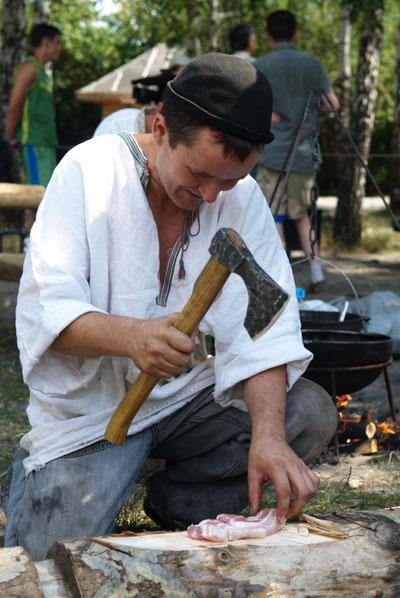 Кузнец рубит мясо для приготовления обеда на празднике Дня кузнеца в Пирогово. Фото: Владимир Бородин/The Epoch Times