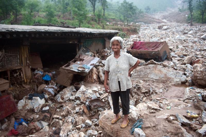 Пекін, Китай, 26 липня. Літня жінка стоїть біля зруйнованого будинку. Найсильніші за останні два місяці дощі завдали шкоди десяткам тисяч жителів столиці. Фото: AFP/AFP/GettyImages