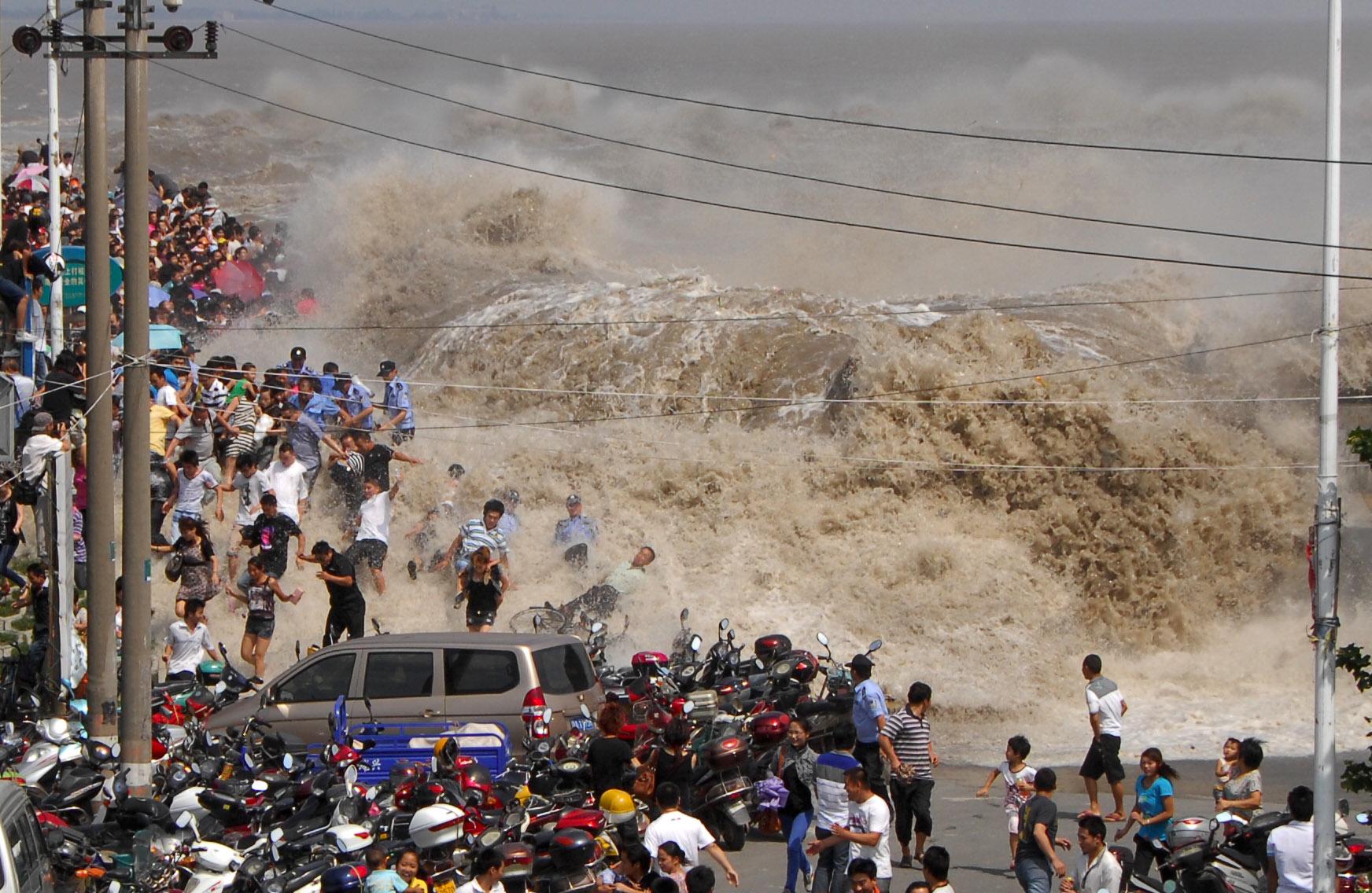 Толпа китайских туристов убегает от приливной волны прорывающейся через плотину на реке Qiangtang в Haining, на востоке Китая провинции Чжэцзян 31 августа 2011 года. Фото: STR / AFP / Getty Images