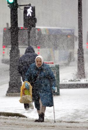 Милуоки. США. Бабушка идёт по улице, в то время как идёт снег. 11 апреля 2007 года. Фото: Darren Hauck/Getty Images