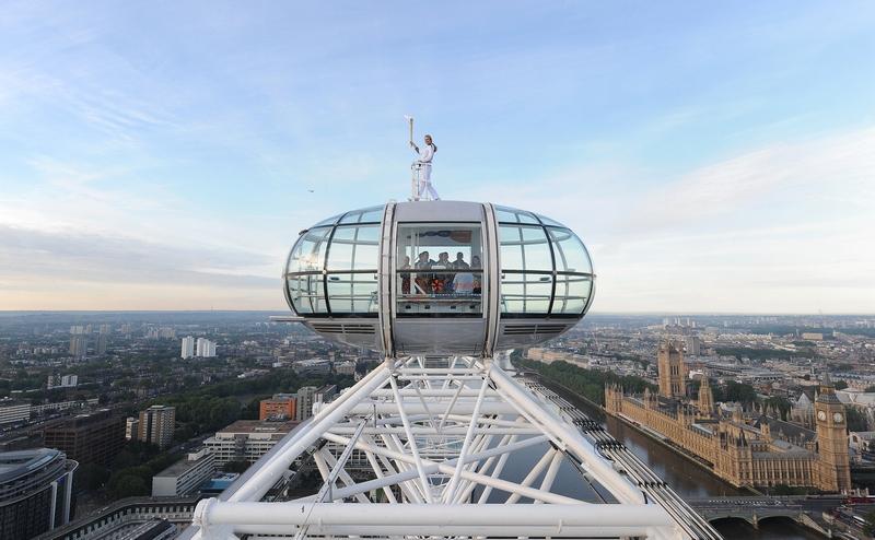 Лондон, Англия, 22 июля. Факелоносец Амелия Хемплеман-Адамс стоит с факелом олимпийского огня на самом верху колеса обозрения «Лондонской глаз». Фото: LOCOG via Getty Images