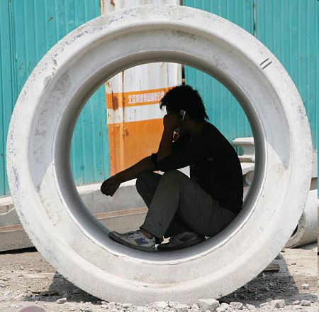 Рабочий разговаривающий по сотовому. Фото: Guang Niu/Getty Images