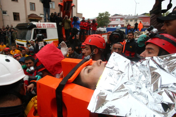 Турецькі рятувальники несуть Семіху Карадуман, мати двотижневої дівчинки Азри Карадуман. Еріш, 25 жовтня 2011 року. Фото: Adem Altan/Getty Images