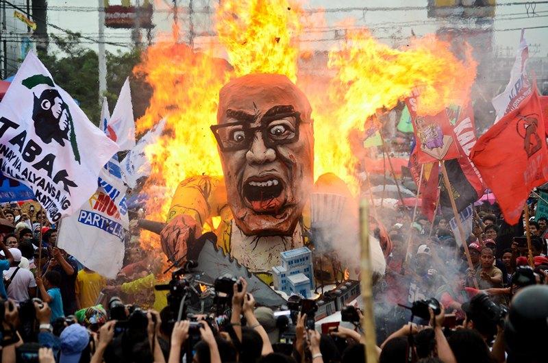 Кесон, Филиппины, 22 июля. Демонстранты сжигают чучело президента Бенигно Акино во время его обращения к конгрессу. Фото: Dondi Tawatao/Getty Images