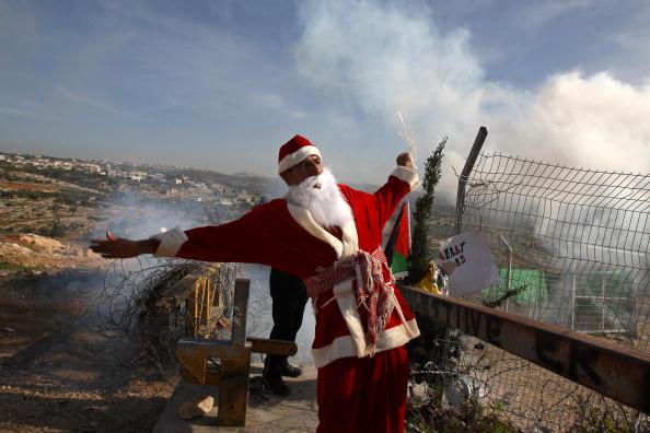 Активист в костюме Санты призывает к миру на Западном берегу реки Иордан. Фото: ABBAS MOMANI/AFP/Getty Images