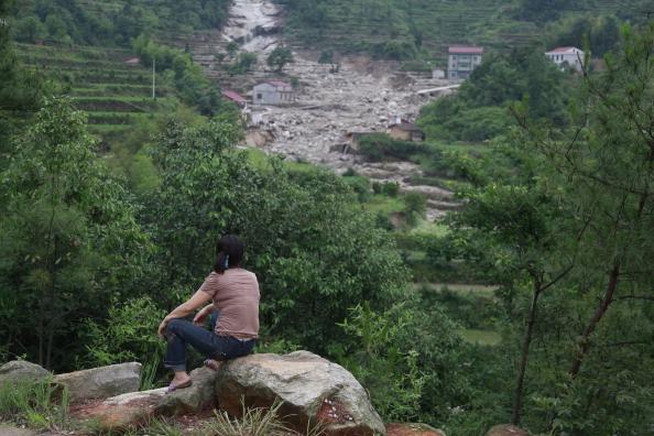 Місцева мешканка дивиться на зруйновані зсувом будови. Провінція Хунань, Китай. Фото: STR/AFP/Getty Images