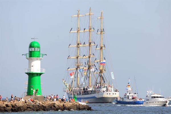Российское учебное парусное судно Мир проходит мимо мола с маяком. Фото: Archiv Hanse Sail Rostock