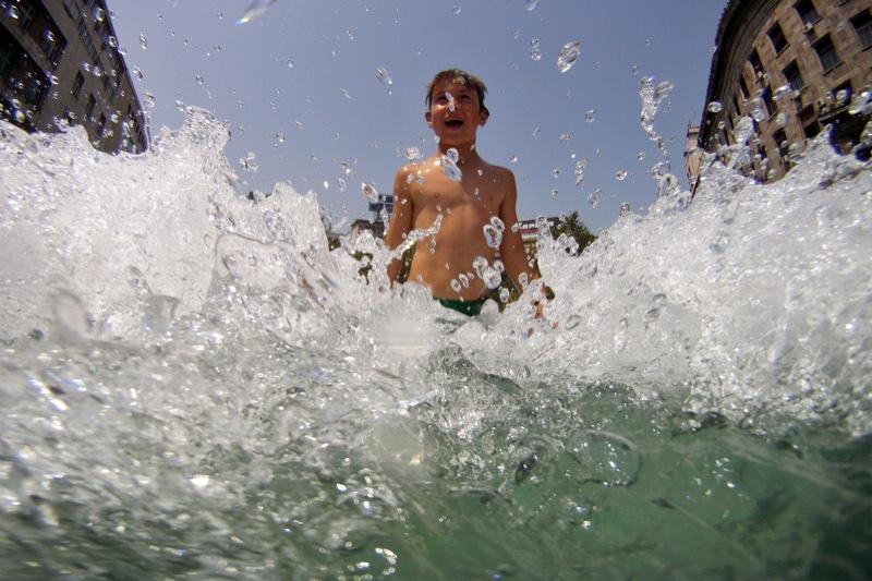 Мальчик охлаждается, играя в фонтане. Фото: ANDREJ ISAKOVIC/AFP/Getty Images