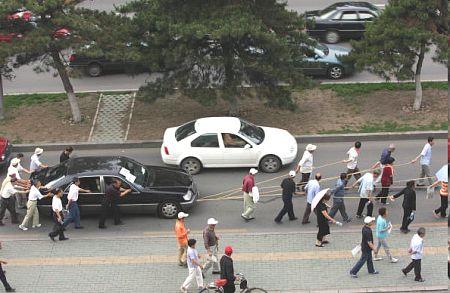 Чанчунь. Уволенные рабочие тащат автомобиль своего начальника, чтобы продать и получить зарплату, не выдаваемую им несколько лет. Фото: Getty Images