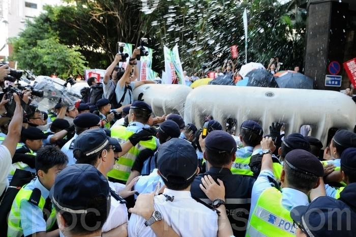 Поліцейські усмиряють демонстрантів перцевої водою. Фото: Велика Епоха