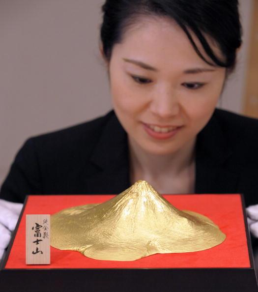 Сотрудник японской ювелирной компании демонстрирует гору Фудзи, сделанную из золота, которая является самой высокой горной вершиной в Японии. Фото: TOSHIFUMI KITAMURA/AFP/Getty Images