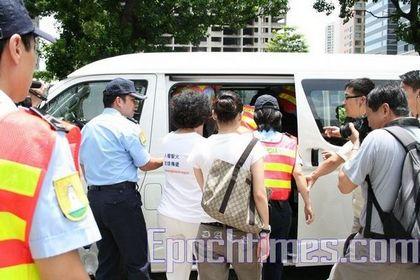 Полицейские сажают в машину Ху Нанбин, одетую в футболку с символикой Эстафеты. Фото: Ан Чи/ The Epoch Times