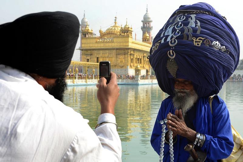 Амрітсар, Індія, 18листопада. Сикхський воїн-ніханг (праворуч) позує перед фотографом. Для створення високого тюрбана, що прикрашає голову ніханга, необхідно до 300метрів тканини. Фото: NARINDER NANU/AFP/Getty Images