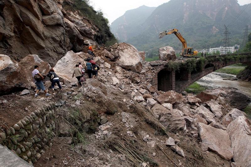 Південний схід провінції Сичуань, Китай, 21 квітня. Люди пробираються до мосту дорогою, зруйнованою сильним землетрусом. Фото: STR/AFP/Getty Images