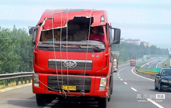 Несмотря на сильный ветер, водитель уверенно ведёт грузовик со скоростью почти 100 км/час через три провинции. В его кабине два человека укрылись одеялами. Провинция Хэбэй. август 2011 год. Фото: news.ifeng.com