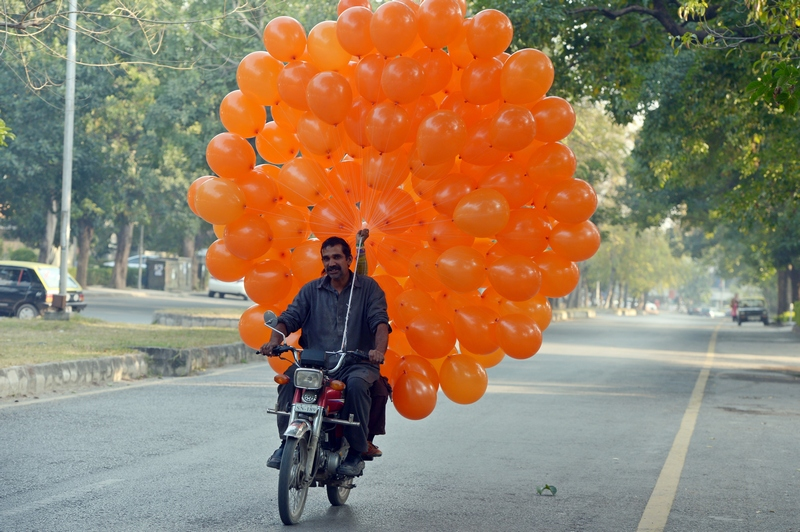 Ісламабад, Пакистан, 22грудня. Торговець везе на продаж надувні кульки. Фото: FAROOQ NAEEM/AFP/Getty Images