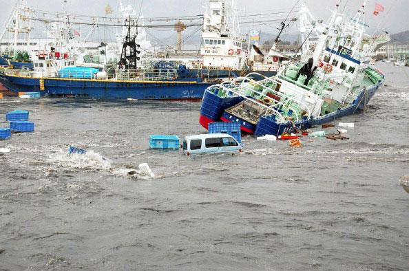 Рыболовецкие суда и автомобили после цунами в порту Onahama в городе Иваки в префектуре Фукусима вызванного сильным землетрясением в Японии 11 марта 2011 года. Фото: AFP PHOTO / FUKUSHIMA MINPO via JIJI PRESS