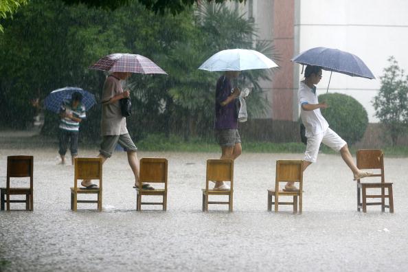 Студенты идут на занятия по «мосту» из стульев. г. Ухань, провинция Хубэй. Фото: STR/AFP/Getty Images