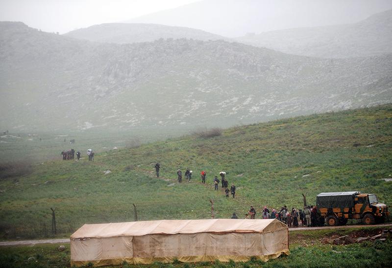 Сирийские беженцы подходят с сирийской стороны к турецкой границе с Сирией в районе Рейханлы, 14 марта 2012 года они пытаются проникнуть в Турцию. Фото: BULENT KILIC/AFP/Getty Images