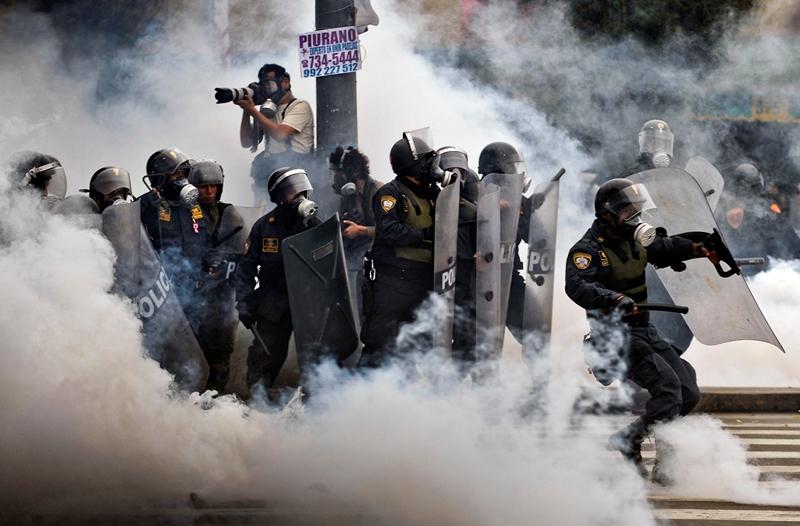 Лима, Перу, 27 июля. Клубы слезоточивого газа окружают отряд полиции во время столкновений со студентами и рабочими, недовольными новыми законами правительства. Фото: ERNESTO BENAVIDES/AFP/Getty Images
