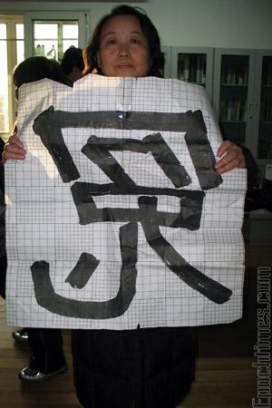 Женщина держит плакат с иероглифом «НЕСПРАВЕДЛИВОСТЬ». Фото: Великая Эпоха