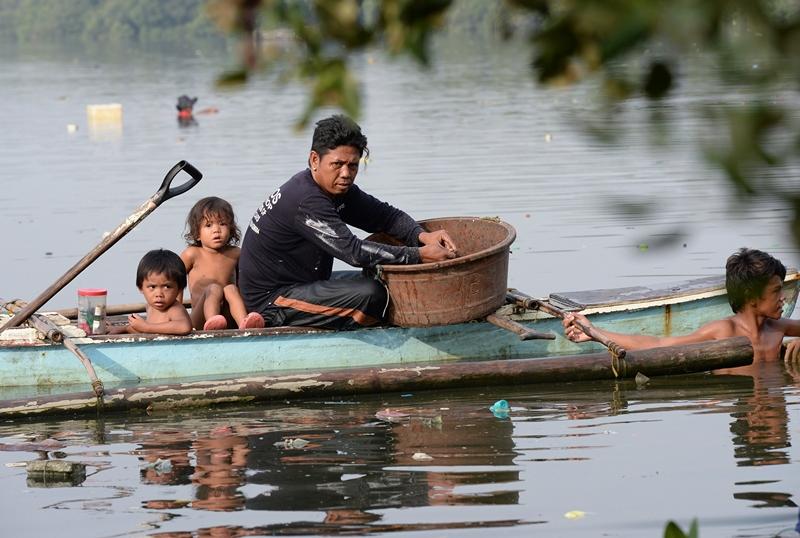 Паранак, Філіппіни, 8 червня. Рибалка разом зі своїми дітьми ловить крабів. Фото: TED ALJIBE/AFP/Getty Images
