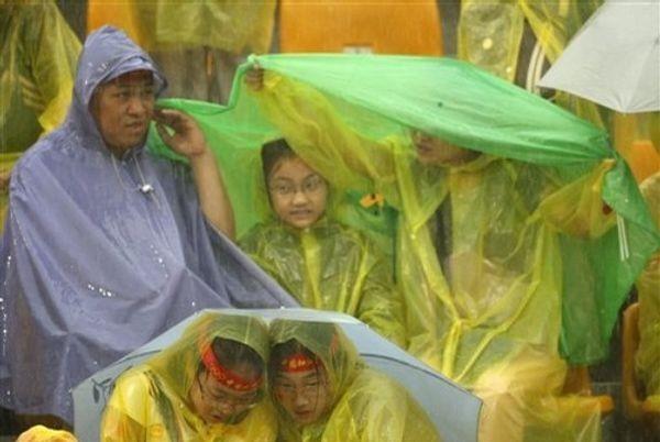 Зрители под проливном дожди ждут результатов по соревнованиим по стрельбе из лука среди женщин 10 августа 2008 г. в Пекине. Фото: AFP
