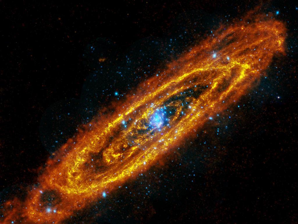 Туманность Андромеды. Оранжевый и жёлтый цвета — инфракрасный диапазон («Гершель»), окрашенные голубым звёзды — рентгеновский диапазон («XMM-Newton»). Фото: ESA/NASA/JPL-Caltech