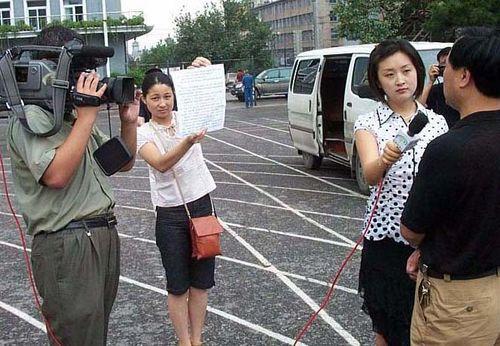 Вот так в Китае берут интервью. Интервьюируемому заранее на бумаге пишут «правильные» ответы на вопросы корреспондента, после чего он читает их перед камерой. Фото с secretchina.com