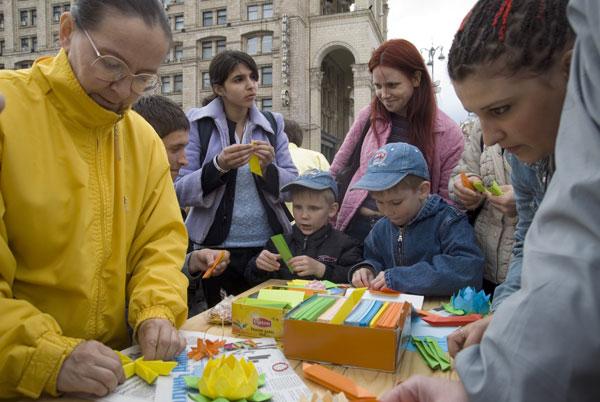 Последователи Фалуньгун учат желающих складывать бумажные лотосы в на площади Независимости в Киеве в Международный День Фалунь Дафа 13 мая 2008 года. Фото: The Epoch Times