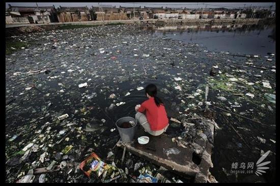 Жителька селища Гуйюй провінції Гуандун пере одяг у місцевому ставку, сильно забрудненому промисловими відходами. 25 листопада 2005. Фото: Лу Гуан
