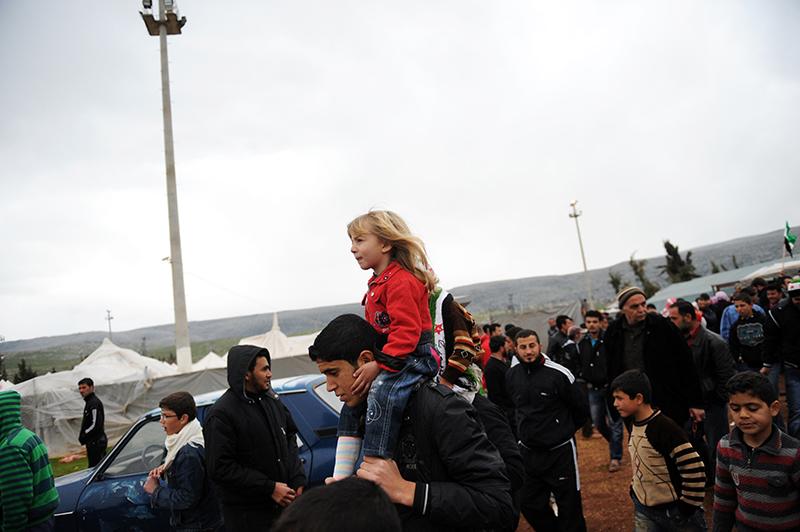 Сирийский беженец с девочкой на плечах во время демонстрации против президента Сирии в лагере беженцев в Турции в районе Рейханлы, 16 марта 2012 года. Фото: BULENT KILIC/AFP/Getty Images