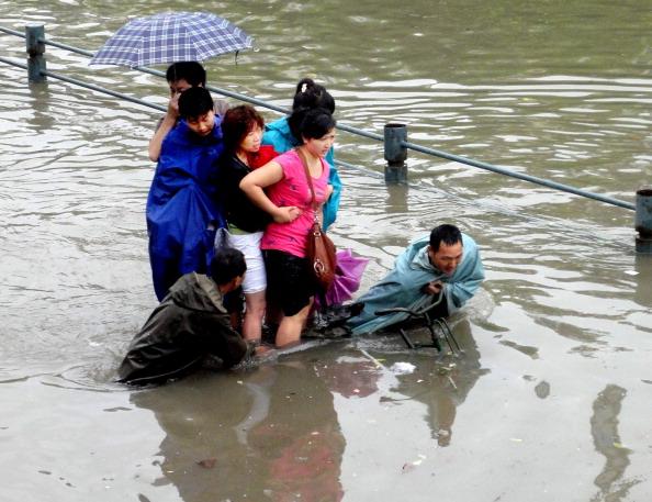 Пешеходы пробираться по затопленной улице после сильного дождя в г. Ухань, провинция Хубэй. Фото: ChinaFotoPress/Getty Images