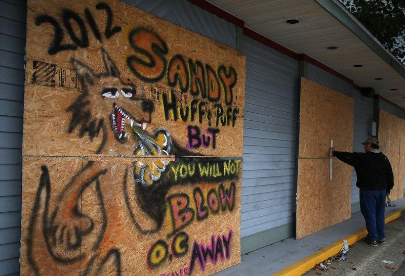 Ошен Сити, США, 28 октября. Владелец парикмахерской закрывает окна фанерными щитами для защиты от приближающегося урагана Сэнди. Фото: Mark Wilson/Getty Images