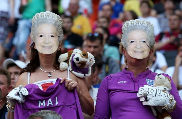 Англійські вболівальники одягнули маски королеви Єлизавети II на матчі між Францією і Англією на Донбас Арені 11 червня 2012 року в Донецьку, Україна. Фото: Scott Heavey/Getty Images