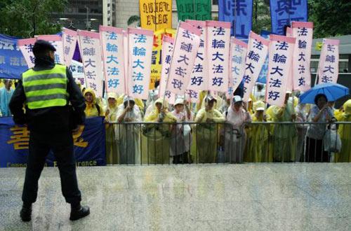 Последователи Фалуньгун пикетируют под дождем у гонконгской гостиницы, в которой остановился Ху Цзинтао. Фото: TED ALJIBE/AFP/Getty Images
