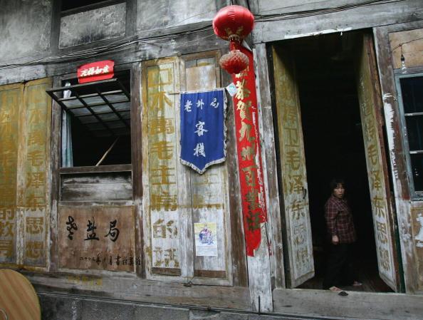 Женщина возле ворот старого дома. Фото: China Photos/Getty Images