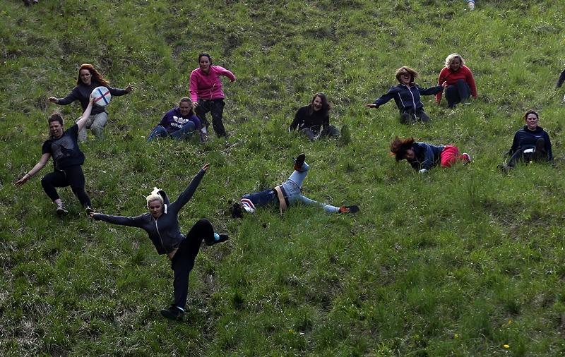 Брокворс, Англия, 27 мая. На холме Купера проходят традиционные экстремальные «сырные гонки». Участникам состязания нужно догнать катящуюся с крутого холма головку сыра. Фото: Matt Cardy/Getty Images