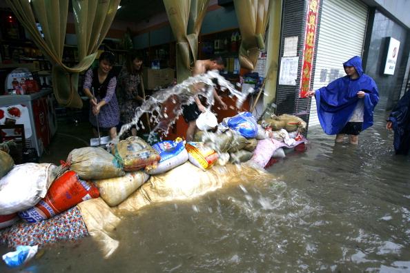 Персонал магазина старательно вычерпывает воду из помещения. г. Ухань, провинция Хубэй. Фото: STR/AFP/Getty Images